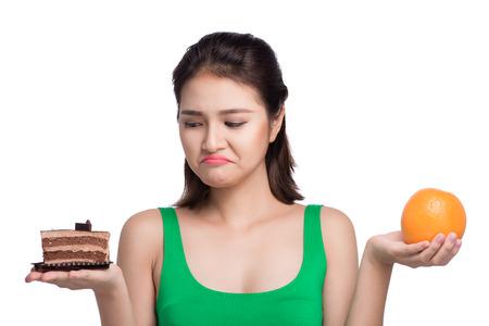 concepto de dieta de drogas. alimentos saludables . hermosa mujer asiática joven elegir entre frutas y dulces Foto de archivo
