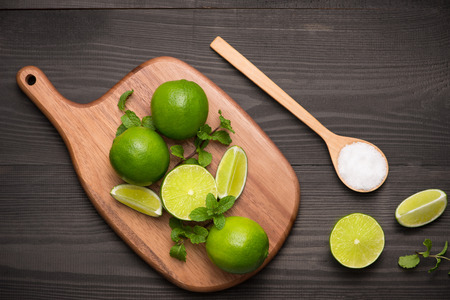 Fresh limes on cutting board on wooden table with spoon of salt. Top view, background.