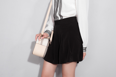 Full-length portrait of beautiful asian woman holding a bag walking over gray background.