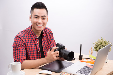Professional photographer. Portrait of confident young man in shirt holding hand on camera while sitting at his desk. Imagens - 86561632