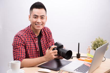 Professionele fotograaf. Portret van de zekere jonge mens in de hand van de overhemdsholding op camera terwijl het zitten bij zijn bureau.