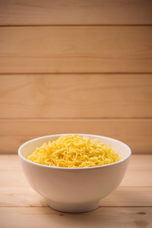 Instant noodles in bowl on wood background Stock Photo