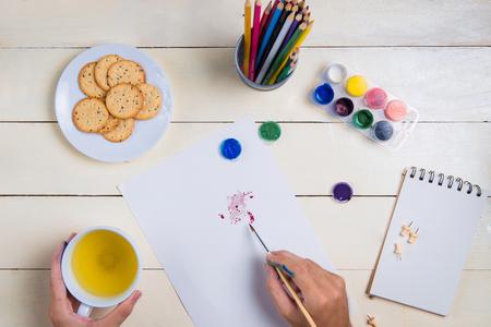 Penseel, schetsboek en aquarel kleuren op tafel.