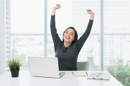 Happy relaxed young woman sitting at her desk with a laptop, stretching her arms