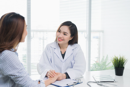 白い医学のコートの医者および患者の美しい女性医者は病院の窓の近くの机に座っている