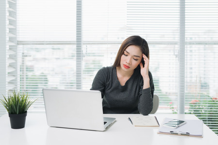 Young asian business woman with tired eyes and headache