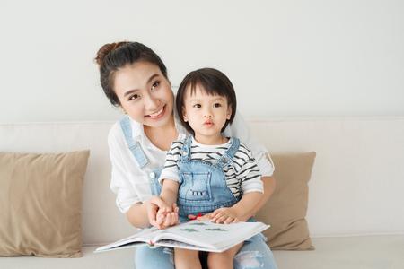 bonne mère aimante jolie jeune mère asiatique lisant un livre à sa fille Banque d'images