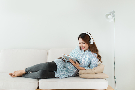 Pretty asian listening to music on couch at home in the living room Reklamní fotografie