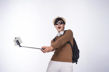 幸せな若いアジア男スマート フォンを介してセルフ ポートレート写真撮影