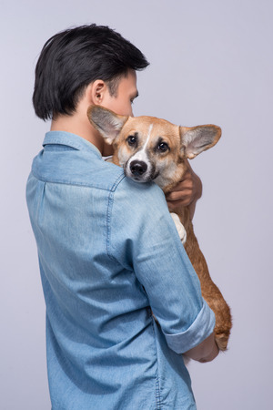 A man snuggling and hugging his dog, close friendship loving in studio background