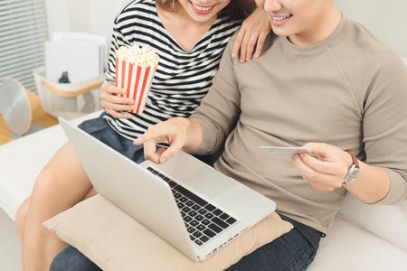 Jonge Aziatische paarbetaling online gebruikend laptop kopend filmkaartje Stockfoto