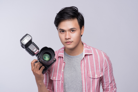 Young asian photographer holding digital camera, while working in studio Stok Fotoğraf
