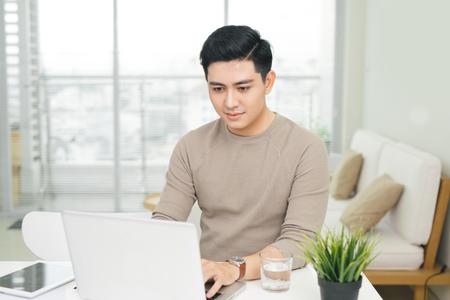 retrato de un joven casual sonriente usando la computadora portátil en casa