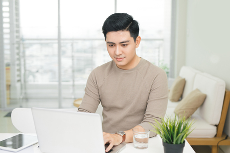 Portrait of a casual smiling young man using laptop at home Foto de archivo