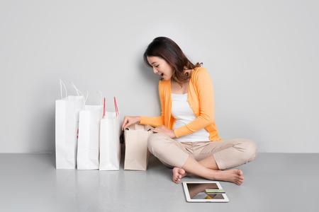 Jonge Aziatische vrouw die online thuis zit die naast rij van het winkelen zakken winkelt