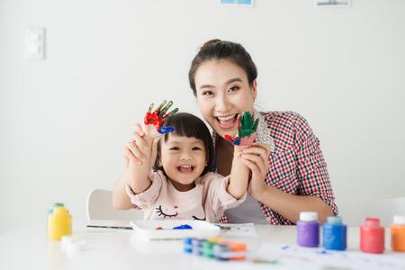 Een gelukkig gezin is aan het schilderen. Moeder helpt haar dochter te tekenen