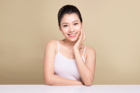 Beauty face. Facial treatment. Young asian woman with clean perfect skin touch her face. Stok Fotoğraf
