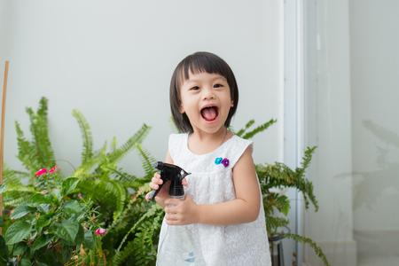 niño cuidando de las plantas. niña linda regar las primeras flores de navidad Foto de archivo