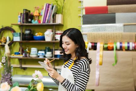 Lächelnder asiatischer weiblicher Florist, der Anmerkungen am Blumenladenschalter macht Standard-Bild - 86952798