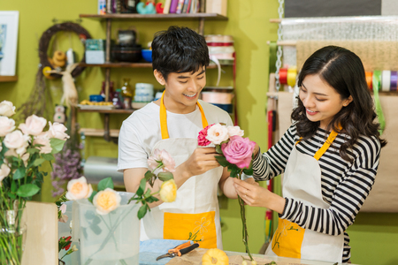 selling service: Male and female florists with beautiful bouquets in flower shop.