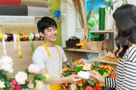 Jonge vrouw die werkt als bloemist die creditcard geeft aan klant