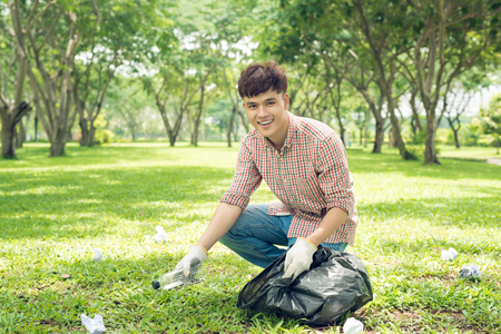 Asian man picking up plastic household waste in park Stock Photo