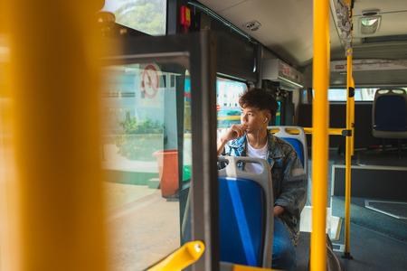 아시아 남자 도시 버스에 앉아 음악을 듣고 창을 통해 찾고. 스톡 콘텐츠 - 87165812