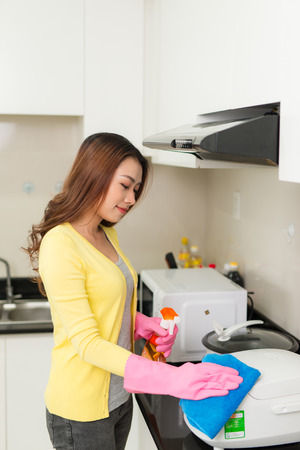 Young housewife wearing rubber gloves  clean kitchen