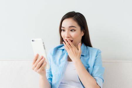 Beautiful excited woman looking at smartphone at home Stockfoto
