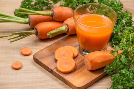 Glass of fresh carrot juice with vegetables on wooden table. Stock Photo