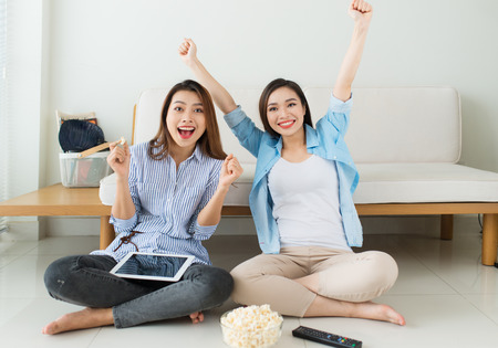 Two girl friends sitting on the floor near the couch watch a movie and eat popcorn, relaxing together. Banque d'images