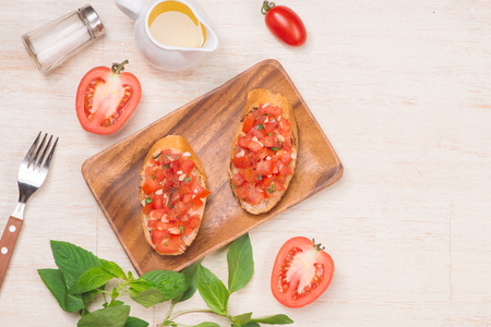 Preparing delicious Italian tomato bruschetta with chopped vegetables, herbs and oil