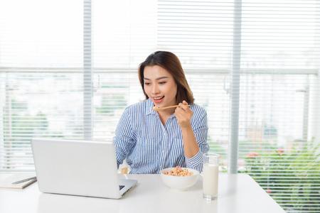 femme d & # 39 ; affaires exécutif manger déjeuner à son lieu de travail Banque d'images
