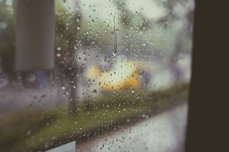 Regen op een raam. Regen op een raam verduistert de buitenkant naar een buitenfocuspatroon. Stockfoto