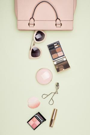 Productos de maquillaje con bolsa de cosméticos sobre fondo de color