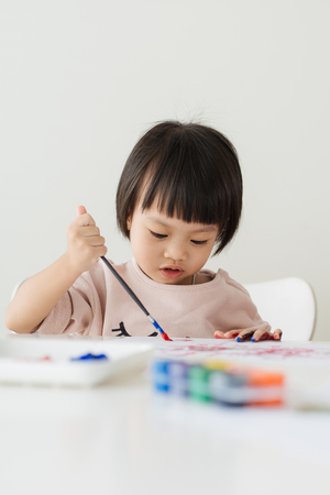 children painting: Little asian girl painting with paintbrush and colorful paints
