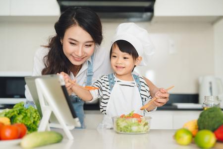 母と娘は台所で昼食を準備し、一緒に楽しんで。