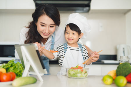 Mother with her daughter preparing lunch in the kitchen and enjoying together. Imagens - 87404615