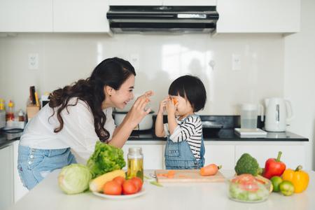 Gelukkige familie in de keuken. Moeder en kind dochter bereiden de groenten en fruit. Stockfoto