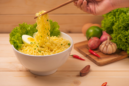 Eating Instant noodles with a wooden chopstick. Stock Photo