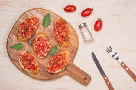 Bruschetta italienne tasty avec du pain garni de tomates et herbes sur planche de bois Banque d'images - 87645776