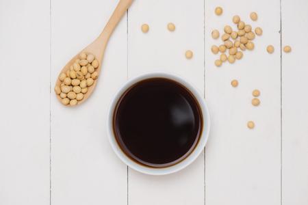 醤油と木製のテーブルに醤油豆 写真素材