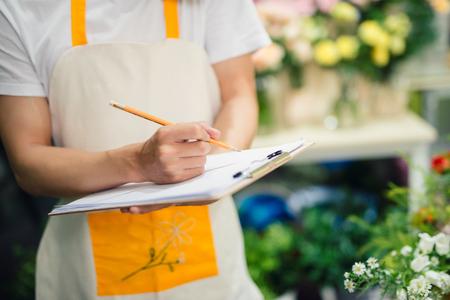 Geerntetes Bild des asiatischen männlichen Floristen, der Anmerkungen am Blumenladenzähler macht Standard-Bild - 87864188