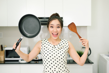 Happy housewife hold up with pan wooden turner in kitchen