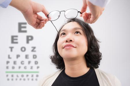 새 안경. 시도하는 아시아 여자 안경을주는 검안사