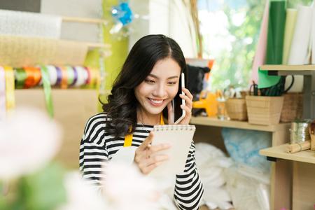 スマートフォンで通話し、フラワーショップカウンターでノートを作る女性花屋