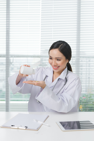 Female doctor smiling looking and holding box of medicine in her hand.