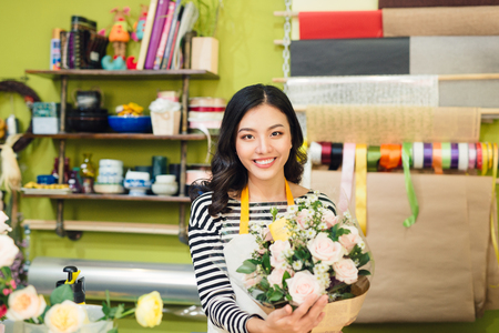 Beautiful asian female florist holding bouquet of flowers