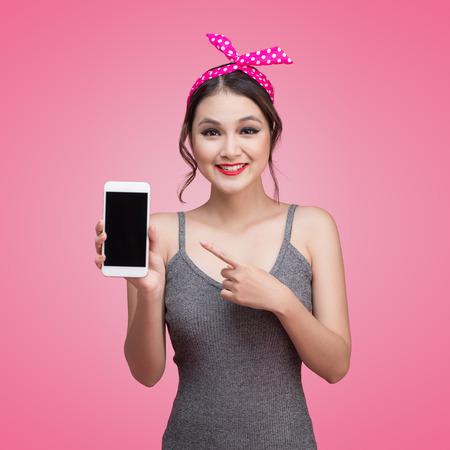 ピンまで化粧と髪型携帯電話とピンクの背景の上の美しい若いアジア女性