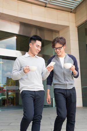 Twee glimlachende zakenlieden die en in de stad lopen spreken Stockfoto